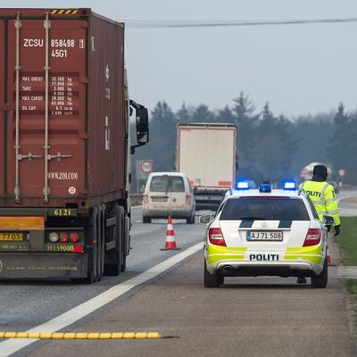 Poliisiauto vilkut päällä moottoririen pientareella, vieressä neljä poliisia huomioliiveissä. Kyltit kertovat, että ollaan Tanskan kuningaskunnan ja EU:n rajalla.