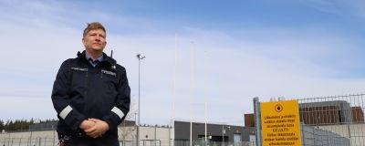 En man i uniform står utanför Åbo fängelse. Till vänster en gul skylt där det står att obehöriga inte har tillträde.