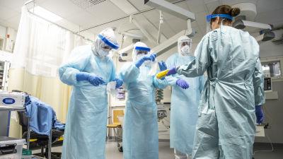 Personalen vid Kuopio universitetssjukhus övar hur man klär på sig och använder skyddsdräkt.
