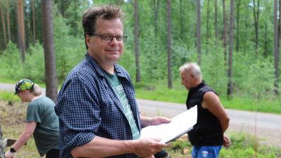 En man med glasögon ser in i kameran. I handen har han ett papper.