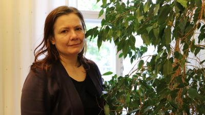 Kristina Friman står bredvid en krukväxt.