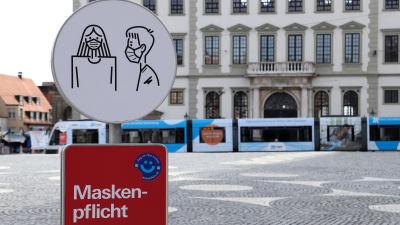 Skylt infomerar om att det är obligatoriskt att bära munskydd utanför rådhuset i Augsburg