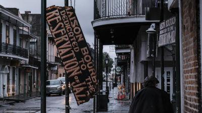 Gatuvy med en skadad skylt som hänger snett.