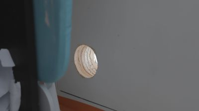 Ett hål som borrats i en balkongdörr, som fungerar som tillfällig ventilation. Hålets diameter är ungefär lika stort som en stor apelsin.