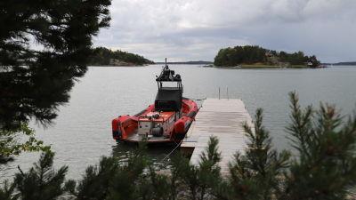 En röd sjöräddningsbåt som är förtöjd vid en brygga.