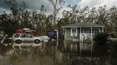 Ett hus och en bil ligger översvämmade i Barratan utanför New Orleans.