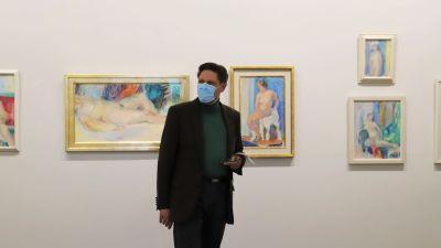 Christian Hoffman visar upp tavlor målade av konstnären Sigrid Schauman.