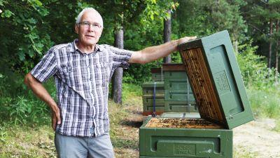En man med glasögon står bredvid en bikupa.