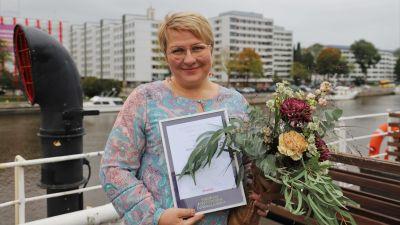 Radioredaktören Maisku Holmström blev vald till årets positivaste Åbobo. Bilden är fotograferad ombord på båten Ukko-Pekka I bakgrunden Aura å, i handen håller Holmström ett diplom och en blombukett.