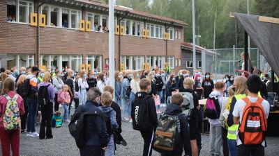 Meri-Porin koululaisia seisoskelee koulun pihalla lavan edessä. Kaksi pikkutyttöä julistaa koulurauhan
