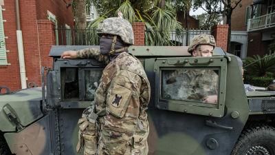 Soldater i kamouflagedräkt och munskydd står bredvid ett militärfordon.
