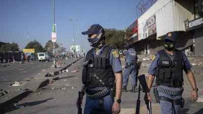 Polisen försöker stoppa plundring i förorten Alexandra i Johannesburg. Tre poliser står med hagelgevär utanför ett köpcenter med demonstranter i bakgrunden.