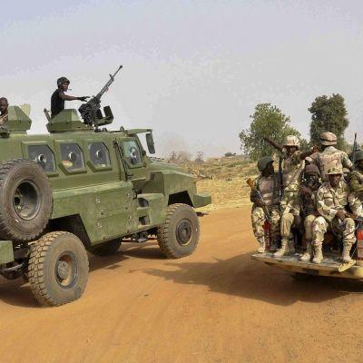 Vihreän, suuren sotilasmaasturin katolla on kaksi sotilasta aseiden kanssa. Pienemmän auton lavalla istuu seitsemän sotilasta. Taustalla näkyy erämaata.