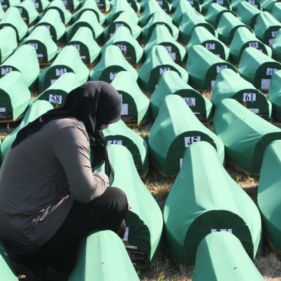 Bosnialainen nainen suri hauta-arkkujen luona Potocarin muistopaikalla Srebrenicassa. Yhteensä 520 uudelleentunnistettua ruumista haudattiin joukkosurman 17-vuotismuistopäivän yhteydessä.