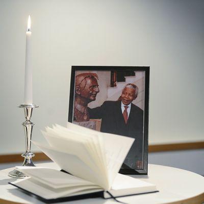 Nelson Mandelan valokuva, surunvalittelukirja ja kynttilä ovat pyöreän valkoisen pöydän päällä Tukholmassa 6. joulukuuta.
