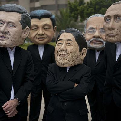 Aktivister porträtterar världsledarna vid klimatmötet i Lima den 12 december 2014.