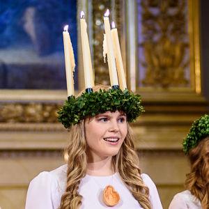 Finlands Lucia 2016 Ingrid Holm iklädd ljuskrona och vit luciadräkt med tärnor i Helsingfors domkyrka.