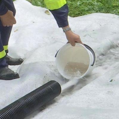 Man håller i ett ämbar medan vatten pumpas ut ur en tjock slang.