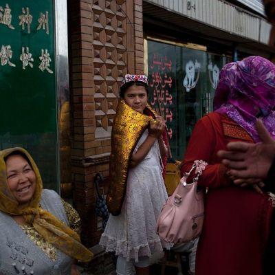 Värikkäisiin asuihin pukeutuneita naisia ja tyttö seinän vierustalla.