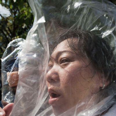 Hallituksen vastainen mielenosoittaja suojasi päänsä muovipussilla kyynelkaasua vastaan Bangkokissa 1. joulukuuta.