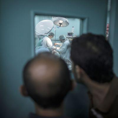 Miehet seurasivat Shifan-sairaalan ensiapuosastolla käynnissä olevaa operaatiota, jossa lääkärit koettivat perlastaa Israelin torille tekemässä iskussa vakavasti loukkaantuneen palestiinalaisen 30. heinäkuuta.