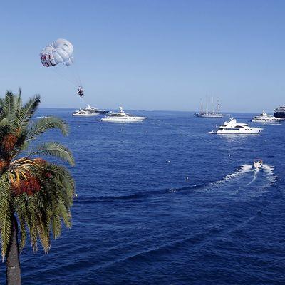 Monacon rannan edustalla on paljon huviveneitä. Taivas on sininen ja aurinko paistaa.