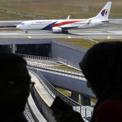Varjossa olevat mies ja nainen keskustelevat, kun taustalla Malaysia Airlines -lentoyhtiön lentokone nousee kiitoradalla.