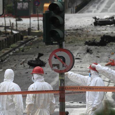 Miehet valkoisissa haalareissaan - poliisin erikoisryhmä - viittovat käsillään kohti pommi-iskun tarkkaa räjähdyspaikkaa.