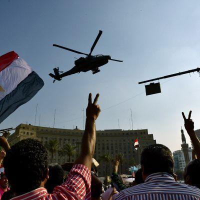 Ihmiset näyttävät voitonmerkkejä ja liehuttavat lippuja. Taivaalla kiertää myös yksi helikopteri.