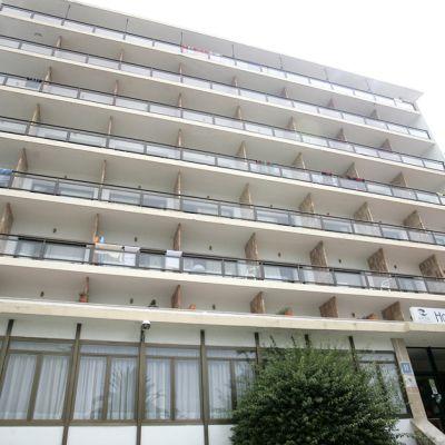 Kuva seitsemän kerrosta korkeasta vaaleasta hotellista.