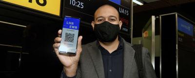 Passagerare visar upp sin mobil. Där syns en QR-kod som bevisar att han testat negativt för covid-19.