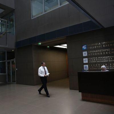 Ateenan pörssi suljettuna, mies kävelee tyhjässä aulassa.