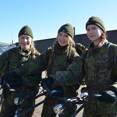 Kolme lukiolaistyttöä polkupyörineen maastopuvuissa