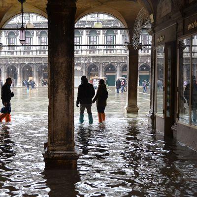Turisteja veden valtaamassa Venetsiassa. Turistit kahlaavat Pyhän Markuksen torilla hätävaraksi ostetuissa oransseissa ja vaaleansinisissä kumisaappaissa.