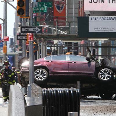 Punainen tai kastanjanruskea auto seisoo tolppien päällä, oikeanpuoleiset renkaat ilmassa. Auton ympärillä häärii palomiehiä. Taustalla näkyy hälytysajoneuvoja.