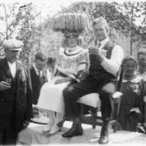 Svartvit, gammal bild av festklätt brudpar på scen