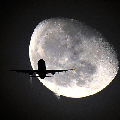 Lentokoneen siluetti kuuta vasten.