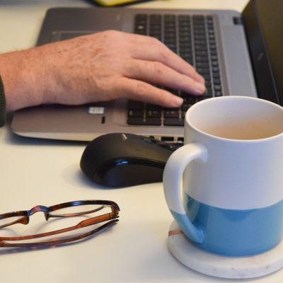 Miehen käsi käyttelee tietokonetta. Pöydällä kahvikuppi ja silmälasit.