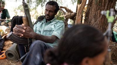 En rebellsoldat sitter och väntar under ett träd och lutar sig mot stammen med ett vapen i famnen.