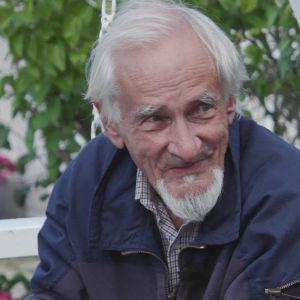 Äldre man i vitt hår och skägg sitter i vitmålad trädgårdsgunga och pratar.