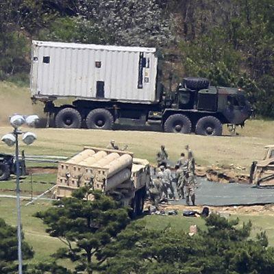 Ohjuspuolustusta pystytetään golfkentälle. Armeijan auto tuo valkoista konttia. Etualalla sotilaat puuhaavat jonkin ohjuslavetin kanssa.