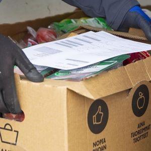 kauppias Jukka Kivioja pakkaa ostoksia pakettiautoon.