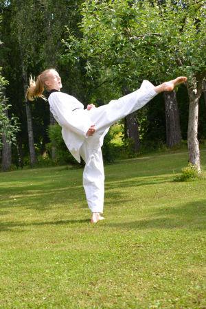En ung kvinna i taekwondodräkt sparkar upp i luften. Hon står framför en röd husvägg.