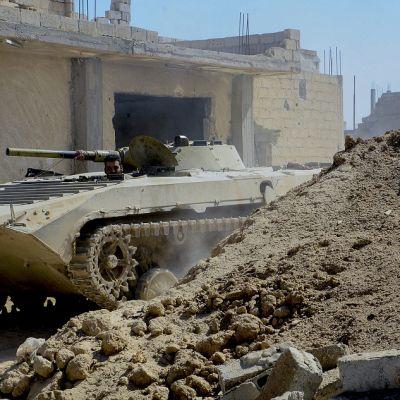 Panssarivaunu on kadulla sorakasan takana. Panssarivaunun luukusta kurkistaa mies. Taustalla näkyy tuhoutunutta kaupunkimaisemaa. Taivas on haaleansininen.