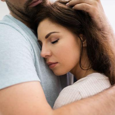 Mörkhårig kvinna kramar om man i ljus skjorta och blundar