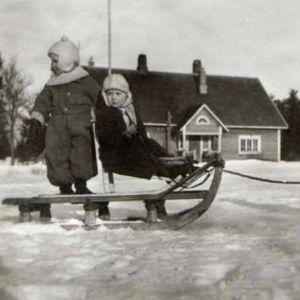 Kolme lasta leikkii kelkalla talvivaatteissa. Kaksi lasta istuu kelkassa ja kolmas vetää.