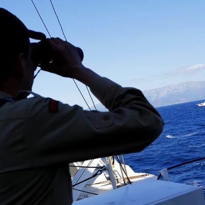 Turkkilainen rajavartia katselee kiikareilla merelle.