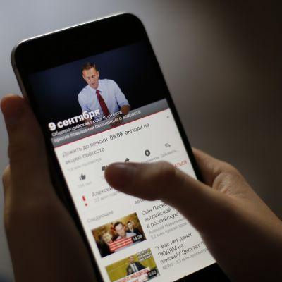 Naisen kädessä on älykännykkä. Älykännykän ruudulla näkyy Aleksei Navalnyi puhumassa videolla mustaa taustaa vasten, yllään vaalea kauluspaita hihat käärittyinä ja kaulassaan kravatti.