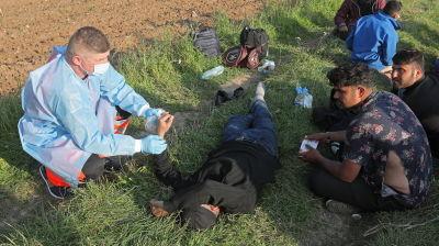 Ambulanspersonal behandlar afghanska migranter i skogen vid gränsen mellan Belarus och Polen.