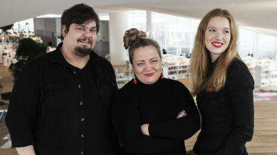 Tre svartklädda personer står bredvid varandra. I bakgrunden syns bokhyllor.